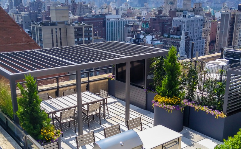 pergola covered rooftop deck with grill and city views