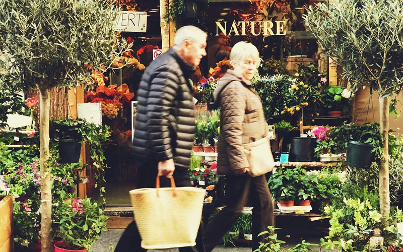 elderly couple in jackets walk in front of nature store front displaying various potted plants